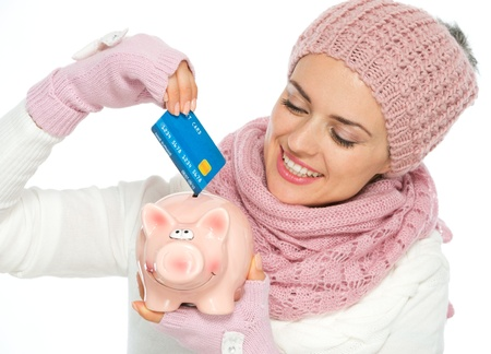 Smiling woman in knit scarf, hat and mittens putting credit card in piggy bank Stock Photo - 15892902