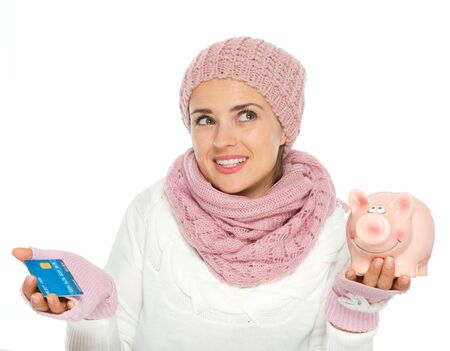 Confused woman in knit winter clothing holding credit card and piggy bank Stock Photo - 15892867