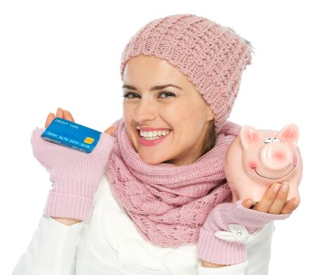 aghast: Smiling woman in knit winter clothing holding credit card and piggy bank