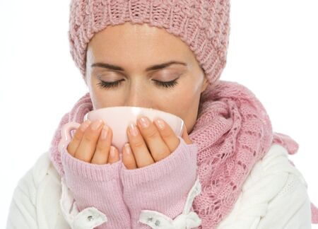 Woman in knit scarf, hat and mittens drinking hot beverage photo
