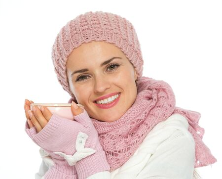 Happy woman in knit scarf, hat and mittens holding cup of tea photo