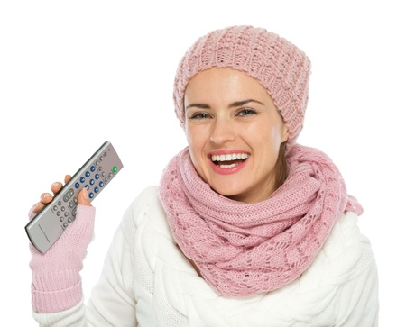 Happy woman in knit winter clothing holding TV remote control Stock Photo - 15892842
