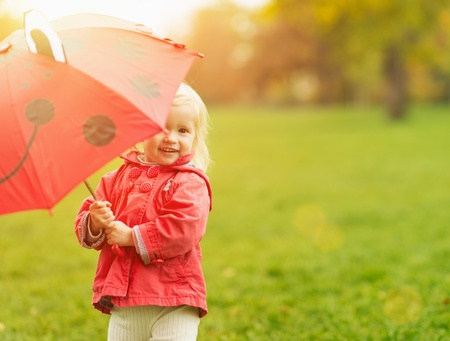 environmentalism: Smiling baby looking out from red umbrella