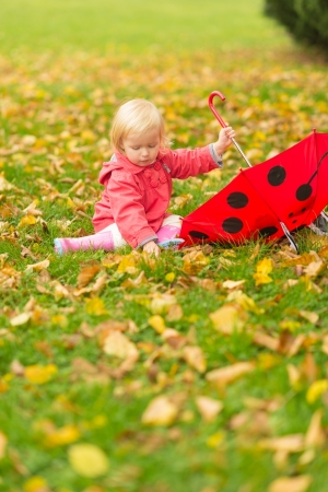 Baby with red umbrella collecting fallen leaves Stock Photo - 16084852
