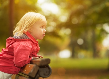 Baby leaning on bench and looking on copy space Stock Photo - 16084821
