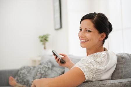 divan: Mujer feliz que pone en el sof� y la celebraci�n de tel�fono celular