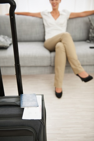 Closeup on suitcase with passport and air ticket and woman in background Stock Photo - 16084779