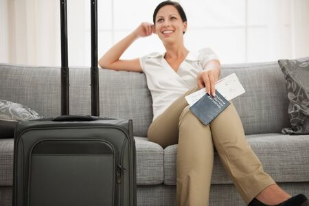 business travel: Dreaming woman with passport and air ticket sitting on couch