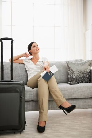 Dreaming woman with passport and air ticket sitting on sofa Stock Photo - 16084845