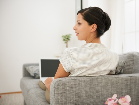 Woman laying on sofa and working on laptop. Rear view Stock Photo - 16084794