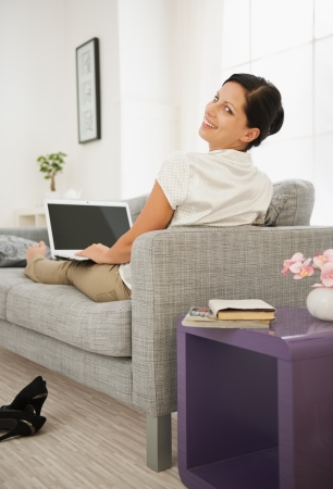 Woman laying on sofa and using laptop. Rear view Stock Photo - 16084822