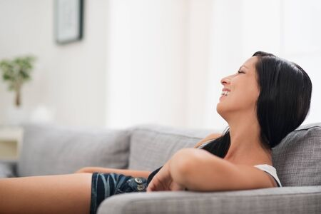 Smiling young woman laying on sofa Stock Photo - 16084750