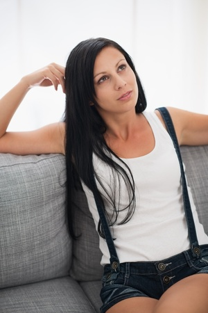 Thoughtful young woman sitting on sofa Stock Photo - 16084843