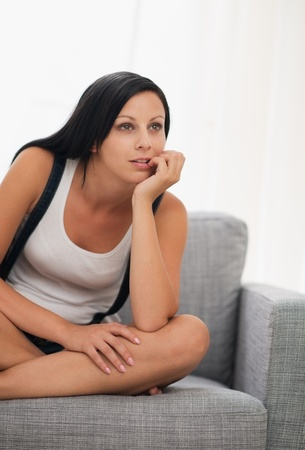 Thoughtful young woman sitting on couch Stock Photo - 16084832