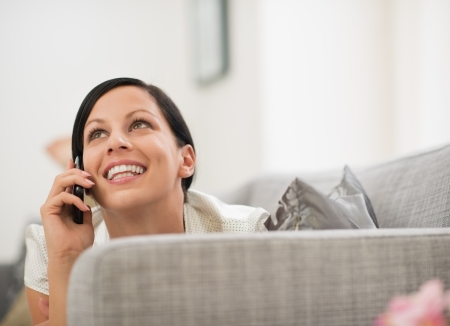 Happy young woman laying on sofa and speaking mobile phone Stock Photo - 16084790