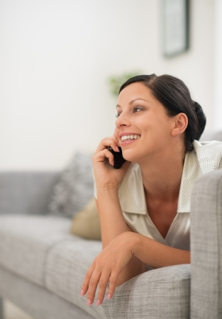 Happy young woman laying on couch and speaking cell phone Stock Photo - 16084829