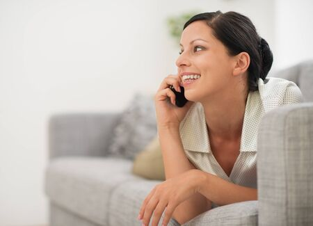 Happy young woman laying on sofa and speaking cell phone Stock Photo - 16084824