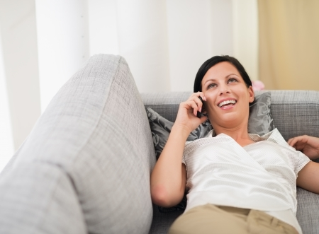 Smiling young woman laying on sofa and speaking mobile phone photo