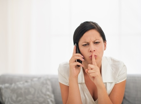 disquieted: Concerned young woman speaking mobile phone and showing shh gesture