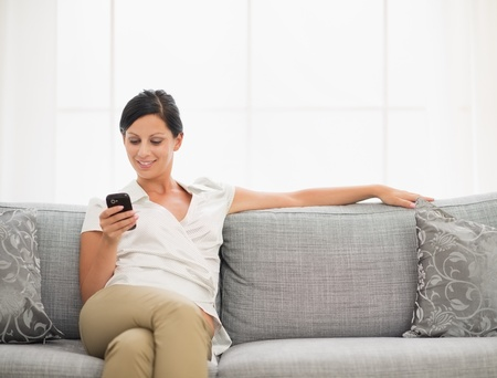 Happy young woman sitting on sofa and reading sms on mobile phone photo