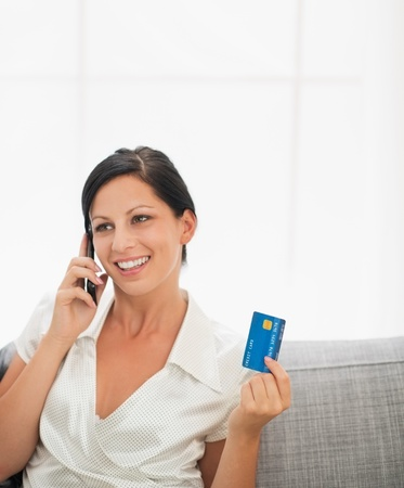 Smiling young woman with credit card and speaking mobile phone Stock Photo - 16084760