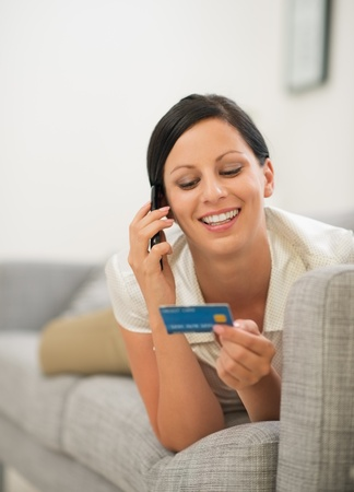 Happy young woman on sofa holding credit card and speaking mobile phone photo