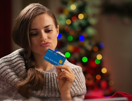 Thoughtful woman in front of Christmas tree holding credit card Stock Photo - 16192489