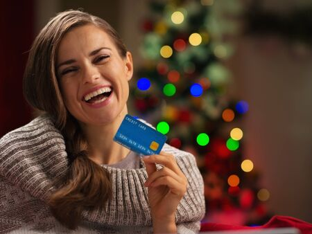 Smiling woman in front of Christmas tree holding credit card photo