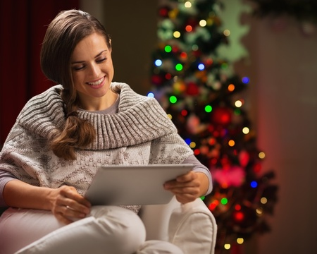 Happy woman sitting with tablet PC in front of Christmas tree Stock Photo - 16192475