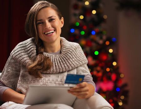 Smiling woman with tablet PC and credit card in front of Christmas tree photo