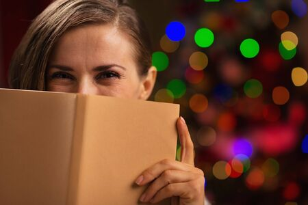 Happy woman hiding behind book in front of Christmas lights Stock Photo - 16192492