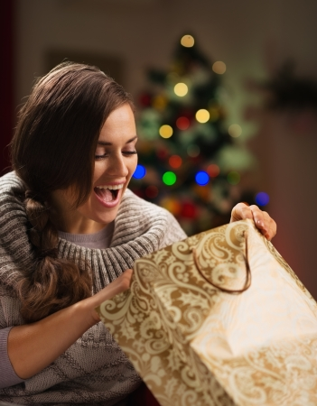 christmas spending: Happy woman in front of Christmas tree looking in shopping bag Stock Photo