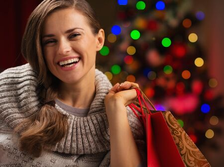 christmas shopping: Happy woman with shopping bag in front of Christmas lights Stock Photo