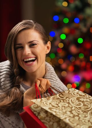 Smiling woman with shopping bag in front of Christmas lights Stock Photo - 16192430