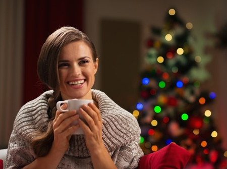 Smiling young woman with cup of hot chocolate in front of Christmas lights Stock Photo - 16192484