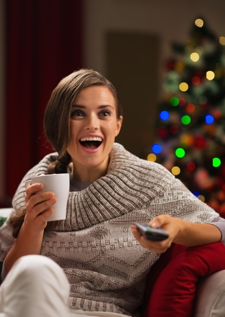 Surprised young woman with cup of hot beverage looking TV Stock Photo - 16192514