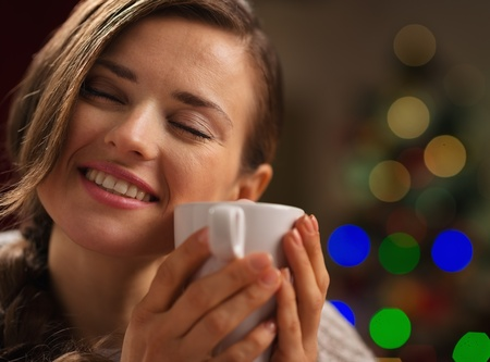 Young woman enjoying cup of hot beverage in front of Christmas lights Stock Photo - 16192479
