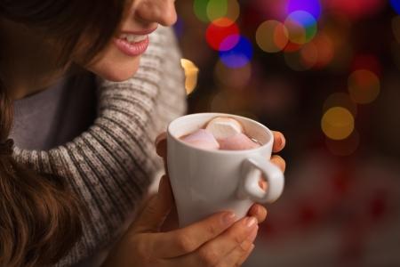 cioccolato natale: Closeup sulla cioccolata calda con i marshmallow in mano di donna felice