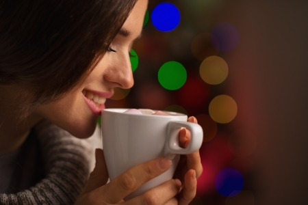 Happy young woman enjoying cup of hot beverage in front of Christmas lights Stock Photo