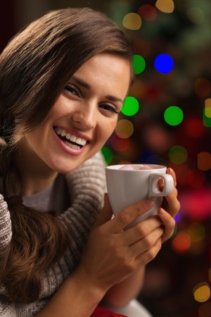 Happy young woman enjoying cup of hot chocolate in front of Christmas lights Stock Photo - 16192418