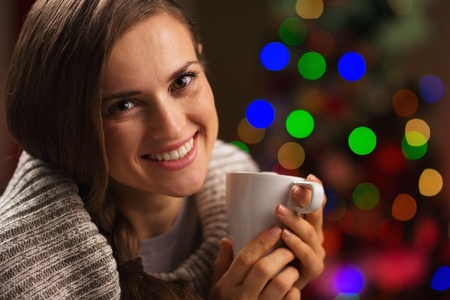 Happy young woman enjoying cup of hot chocolate in front of Christmas lights Stock Photo - 16192526