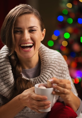 Happy young woman taking out marshmallow from cup of hot chocolate Stock Photo - 16192414