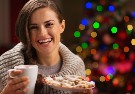 Happy woman holding cup of hot chocolate with marshmallows and plate of Christmas cookies photo