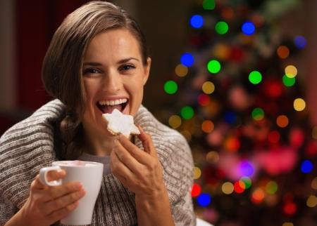 galletas de navidad: Mujer feliz comiendo galletas de Navidad y beber chocolate caliente Foto de archivo