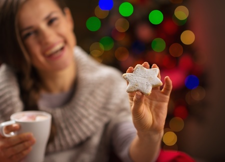 Closeup on hand holding Christmas cookie and happy woman in background Stock Photo - 16192420