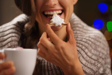 Closeup on happy woman eating Christmas cookie in front of Christmas lights photo