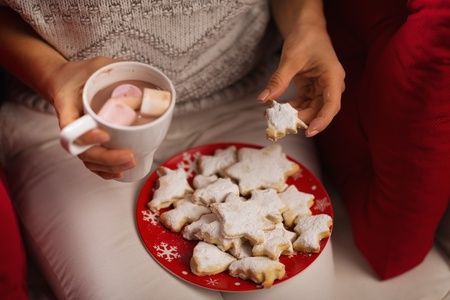 Closeup on woman eating Christmas cookie and drinking hot chocolate with marshmallows photo