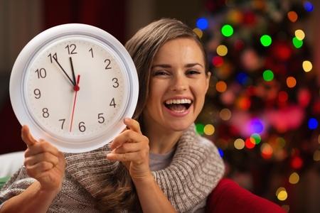 woman clock: Mujer feliz que muestra el reloj en frente del �rbol de navidad Foto de archivo