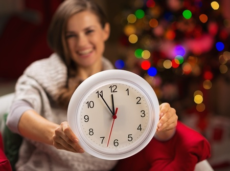 Closeup on clock in hand of happy woman in front of Christmas tree Stock Photo - 16192426