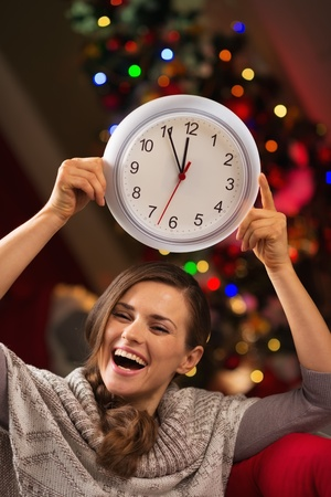 Cheerful woman showing clock in front of Christmas tree Stock Photo - 16192533